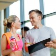 Smiling young woman with personal trainer in gym — Stock Photo #52068731