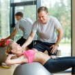 Smiling young woman with personal trainer in gym — Stock Photo #52068867