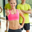 Smiling man and woman showing thumbs up in gym — Stock Photo #52069541