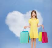 Smiling little girl in dress with shopping bags — Stock Photo