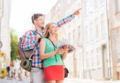 Smiling couple with city guide and backpack — Stock Photo