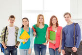 Smiling students with bags and folders at school — Stock Photo