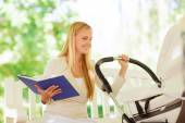 Happy mother with book and stroller in park — Stock Photo