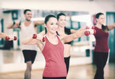 Group of smiling people working out with dumbbells — Stock Photo