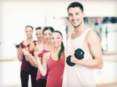 Group of smiling people with dumbbells in the gym — Stock Photo