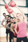 Group of smiling people working out with ball — Foto de Stock
