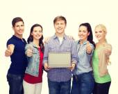 Smiling students with laptop computer — Stock Photo