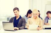 Twee lachende studenten met laptop en tablet pc — Stockfoto