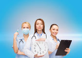 Calm female doctor and nurses with wall clock — Stock Photo