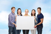 Group of standing students with blank white board — Stock Photo