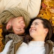 Close up of smiling couple lying in autumn park — Stock Photo #52249897