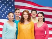 Group of smiling teenagers over american flag — Stock Photo
