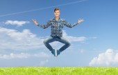 Smiling young man jumping in air — Stock Photo