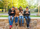 Smiling friends with smartphones in city park — Stock Photo