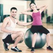 Male trainer with woman doing crunches on the ball — Stock Photo #52301613