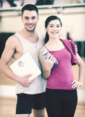 Two smiling people with scale in the gym — Stock Photo