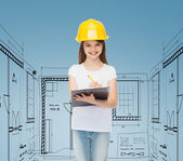 Smiling little girl in hardhat with clipboard — Stock Photo