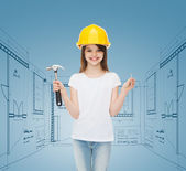 Smiling little girl in hardhat with hammer — Stock Photo