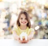 Beautiful little girl holding paper house cutout — Stockfoto