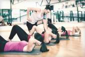 Group of smiling women doing sit ups in the gym — Stock Photo