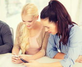 Two teens with smartphones at school — ストック写真