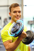 Smiling man with dumbbell in gym — Foto de Stock