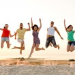 Smiling friends dancing and jumping on beach — Stock Photo #52485657