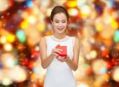 Smiling woman holding red gift box — Foto de Stock