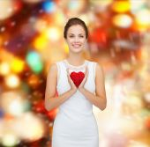 Smiling woman in white dress with red heart — Foto de Stock