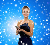 Smiling woman in evening dress with smartphone — Stock Photo