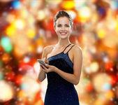 Usmívající se žena ve večerních šatech s smartphone — Stock fotografie
