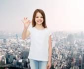 Smiling little girl in white blank t-shirt — Stock Photo