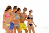Smiling friends in sunglasses on summer beach — Stockfoto