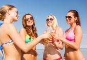 Group of smiling young women drinking on beach — Stok fotoğraf