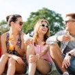 Group of smiling friends sitting on city square — Stock Photo #52554191