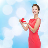 Smiling young woman in red dress with gift box — Photo