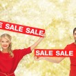 Smiling man and woman with red sale signs — Stock Photo #52629629