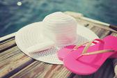 Close-up de chapéu, protetor solar e chinelos na beira-mar — Fotografia Stock