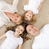 Parents and two girls lying on floor at home — Stock Photo
