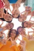 Group of smiling teenagers showing victory sign — Stock Photo