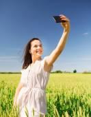 Uśmiechnięte dziewczyny z smartphone na polu zbóż — Zdjęcie stockowe