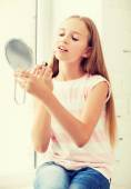 Teenage girl with lip gloss and mirror — Stock Photo