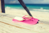 Close up of sunscreen and slippers at seaside — Stock Photo