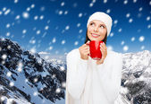 Smiling young woman in winter clothes with cup — Stock Photo