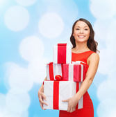 Smiling woman in red dress with gift boxes — Stock Photo