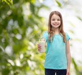 Smiling little girl giving glass of milk — Foto de Stock
