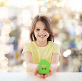 Beautiful little girl holding paper house cutout — Stock Photo