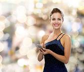 Smartphone ile gece elbisesi içinde gülümseyen kadın — Stok fotoğraf