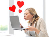 Woman sending kisses with laptop computer — Stock Photo