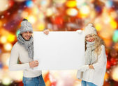 Smiling couple in winter clothes with blank board — Stock Photo
